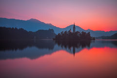 An Island with Church in Bled Lake, Slovenia at Sunrise. Little Island with Catholic Church in Bled Lake, Slovenia at Beautiful Red Sunrise with Castle and Stock Photography