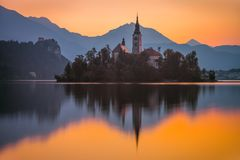 An Island with Church in Bled Lake, Slovenia at Sunrise. Little Island with Catholic Church in Bled Lake, Slovenia at Sunrise with Castle and Mountains in royalty free stock photo