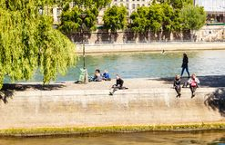 Island of the City. People sit on Quai des Orfevres. Paris. Island of the City. Tourists and locals relaxing in the sun at the Square du. Vert Galant . Paris stock photography