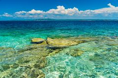 Island with clear blue water. And rocks Royalty Free Stock Photography