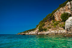 Island cliffs at turquoise sea water. Cliffs at turquoise sea water with emerald hues. Adriatic coast of Hvar island, popular touristic destination at Croatian Royalty Free Stock Images