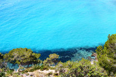 Island cliffs and turquoise sea water Royalty Free Stock Image