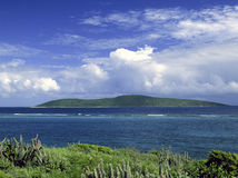 Island and clouds with surf. An island off the coast of St. Croix, Virgin islands, Caribbean Royalty Free Stock Photos