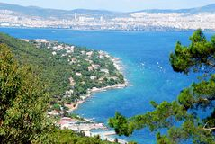 Island coastline and city. Scenic view of coastline of  island with calm blue sea and green tree in Istanbul, Turkey. Prince Islands Royalty Free Stock Image