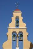 Island Corfu, Paleokastritsa, a man's monastery. High yellow belltower with three bells and a cross Royalty Free Stock Photography