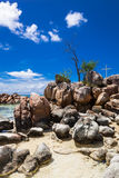Island with a cross. Coast of a rocky island in the sea with a white cross, Praslin, Seychelles, Africa Stock Image
