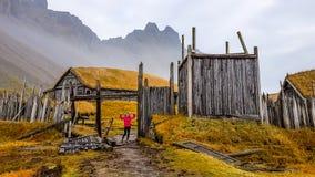 Island - eine Mädchenstellung am Eingang zu einem vikngs Dorf, gelegen unter den hohen Bergen lizenzfreies stockbild