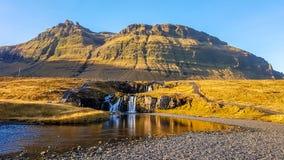 Island - en bedöva vattenfall med högväxta berg bakom royaltyfria bilder
