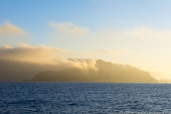 Island engulfed in clouds. Santa Cruz Island in California's Channel Islands is engulfed with early morning cloud cover as it is lit by orange sunlight Royalty Free Stock Images
