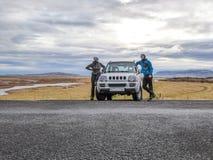 Island - ett par med skelett- framsidask?ldar som framme st?r av en bil royaltyfria bilder