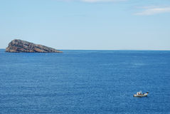 Island and fishing boat. A fishing boat at work next to an island Royalty Free Stock Photo