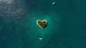 Island in the form of heart in the ocean and flying plane stock video footage