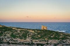Dwejra Bay, Island of Gozo, Malta. Island of Gozo, Malta. Dwejra Bay at sunrise with small watchtower Royalty Free Stock Photography