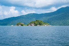 Island green rock mountain on middle sea Stock Photos