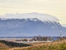 Island - högväxta berg som döljer i molnen av den Pingvellir byn arkivfoto