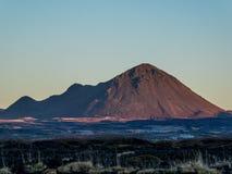 Island - hohe Berge, welche die ersten Sonnenstrahlen des Tages fangen lizenzfreie stockfotografie
