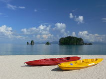 Island Hopping. Colourful Sea Kayaks on a white beach, with blue sea and sky in the background Stock Images