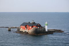 Island with house and lighthouse. House and lighthouse on a small island, in front of the swedish coast Royalty Free Stock Image