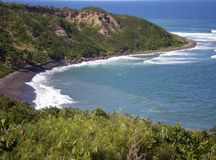 Island inlet. Tropical Caribbean beach with black sand Stock Image