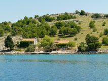 The island Kornat in the Kornati national park. The Croatian isle Kornat with the Statival bay with green bushes and some houses in the Adriatic sea of Croatia Stock Image