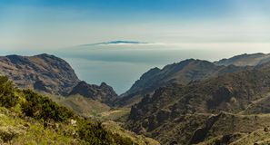 Island of La Gomera, soaring over the horizon, partly covered by the clouds. Bright blue sky. View from 1900 meters of altitude. Deep gorges Teno Natural Park royalty free stock images