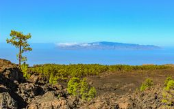 Island of La Gomera, soaring over the horizon, partly covered by the clouds. Bright blue sky. View from 1900 meters of altitude. Teide National Park, Tenerife royalty free stock image
