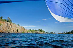 Island on the Ladoga lake. Rocky island on the Ladoga lake (Russia) covered with wood. Blue water, the blue sky with rare clouds. At the right a blue sail royalty free stock photos