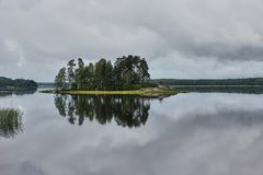 Island on the lake in park Monrepo. In the natural park `Monrepo` in the city of Vyborg there is a lake. There is an island overgrown with trees. The sky Royalty Free Stock Photography