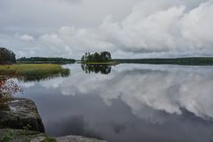 Island on the lake in park Monrepo. Panorama. In the natural park `Monrepo` in the city of Vyborg there is a lake. There is an island overgrown with trees. The Stock Photography
