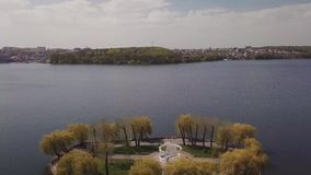 Island in the lake in park in the town view from the drone landing stock video footage