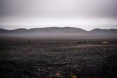 Island-Landschaft, schwarzer vulkanischer Staub und Berge mit Nebel herein Lizenzfreie Stockfotos