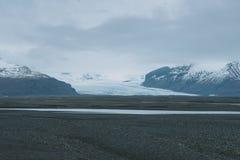 Island-Landschaftsphotographie Gletscher im Hintergrund, der in das Tal von den schneebedeckten Bergen kommt Lizenzfreie Stockfotografie