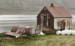 Island landskap i Seydisfjordur Abandoned rostade lantgården och fi Royaltyfri Foto