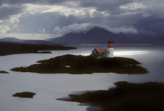 Island lighthouse. Lighthouse on an island back lit by a ray of sun on a stormy day Stock Photos