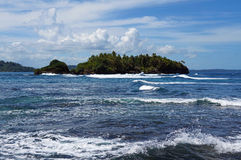 Island with lush vegetation and rough sea Stock Photography