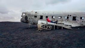 Island - Mädchen, das auf einem zerschmetterten Flugzeug auf einem schwarzen Sandstrand liegt stockfoto