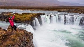 Island - Mädchen und ein mächtiges Godafoss stockfotografie