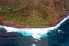 The island of Molokai, Hawaii, coastline from above. Aerial view of green trees and Pacific surf on the coast of the island of Molokai in Hawaii Royalty Free Stock Images