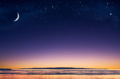 Island Moon. A crescent moon and stars over an island in the Pacific ocean just after sunset Royalty Free Stock Photos