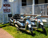 Island Moped Rentals, Block Island, RI. A group of four mopeds are parked in front of a rental sign.  Island Mopeds and Bikes on Block Island use this mopeds to Stock Photography
