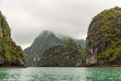 Island mountain tops of ha long bay in Vietnam in clouds royalty free stock photo