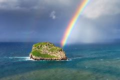 Island named Aketxe in Bermeo with stormy clouds and a rainbow. Small rocky island named Aketxe in Bermeo with stormy clouds and a rainbow Royalty Free Stock Images