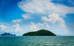 Island in the ocean. Desert island in the ocean and colorful cloudy sky Royalty Free Stock Photo