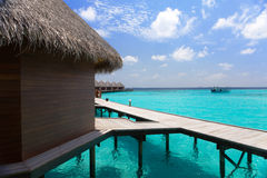 Island in ocean, Maldives. Villa on piles on water Royalty Free Stock Photos