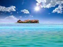 Island in ocean, overwater villas.Sea tropical landscape in a sunny day. Island in ocean, overwater villas Royalty Free Stock Photo