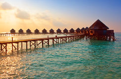 Island in ocean, overwater villas at the time suns. Et. Landscape Royalty Free Stock Images