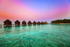 Island in ocean,overwater villas at time sunset Royalty Free Stock Images