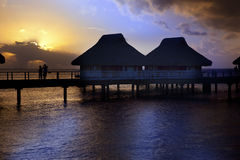 Island in ocean, overwater villas at the time sunset. Royalty Free Stock Photo