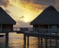 Island in ocean, overwater villas at the time sunset. Royalty Free Stock Photography