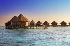 Island in ocean, overwater villas at the time sunset.  Royalty Free Stock Photos